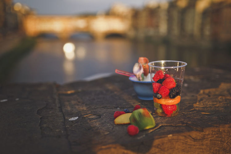 Ripe berries and fruits in a cup for a snack on the parapet of the city bridge. Close-up Drink Drinking Glass Focus On Foreground Food Food And Drink Freshness Fruit Glass Healthy Eating Household Equipment Nature No People Outdoors Refreshment Selective Focus Still Life Table Water Wellbeing