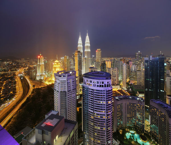 Mid distance view of illuminated petronas towers in city at dusk