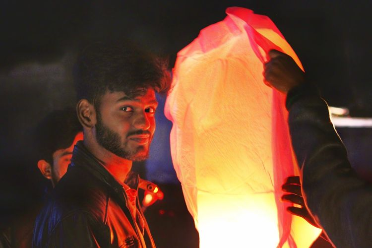Portrait of young man standing by illuminated lighting at night