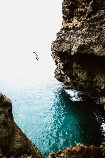 Man jumping from cliff into sea
