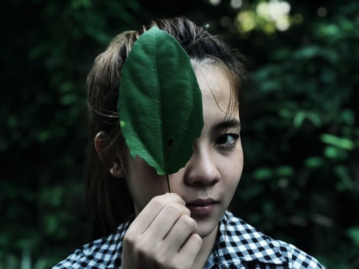 Close-up portrait of woman holding leaf against blurred background