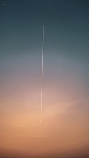 Low angle view of vapor trails against sky during sunset
