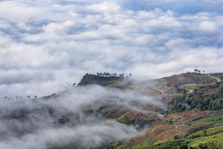 Scenic View Of Mountains Against Cloudy Sky During Foggy Weather