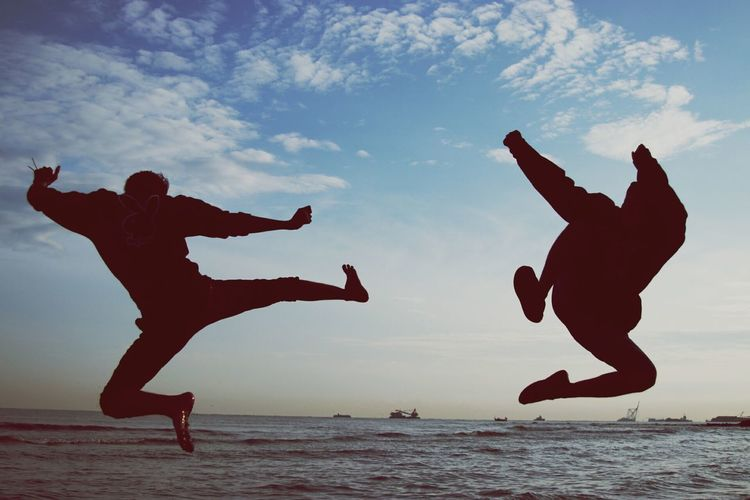 Silhouette friends jumping at beach against sky
