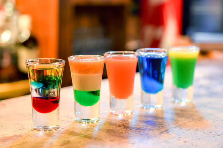 Close-up of colorful cocktail glasses on a bar stand
