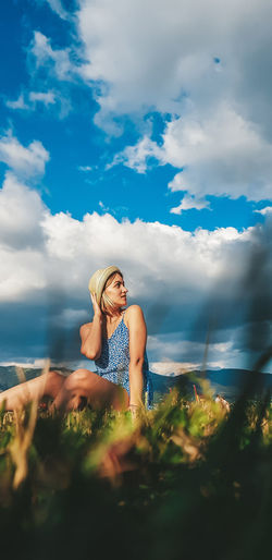 Woman siting by in grassland against sky