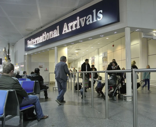 International Arrivals UK Airports Airport Airport Departure Area Chair Clock Communication Day Indoors  Men People Real People Seat Sitting Text Transportation Transportation Building - Type Of Building Waiting Women Postcode Postcards