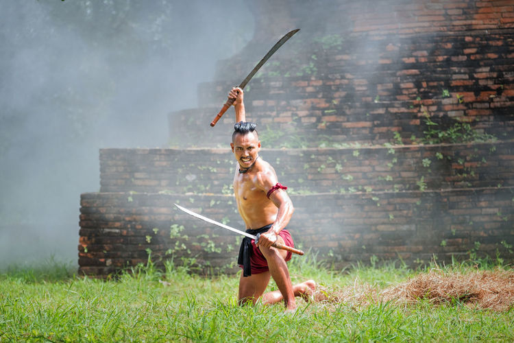 Full length portrait of shirtless warrior with swords on grassy field