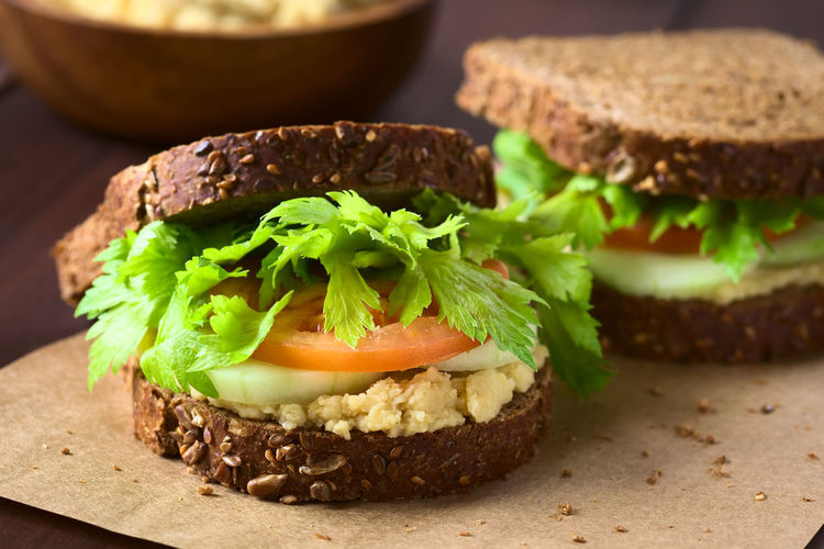 Vegan wholegrain sandwich with celery leaves, tomato, cucumber and chickpea spread or hummus, photographed with natural light (Selective Focus, Focus on the front of the sandwich) Cucumber Garbanzo Raw Vegetarian Vegetarian Food Bread Breakfast Celery Chickpea Food Food And Drink Fresh Healthy Healthy Eating Hummus Leaf Meal Raw Food Sandwich Snack Spread Tomato Vegan Vegetable Wholegrain