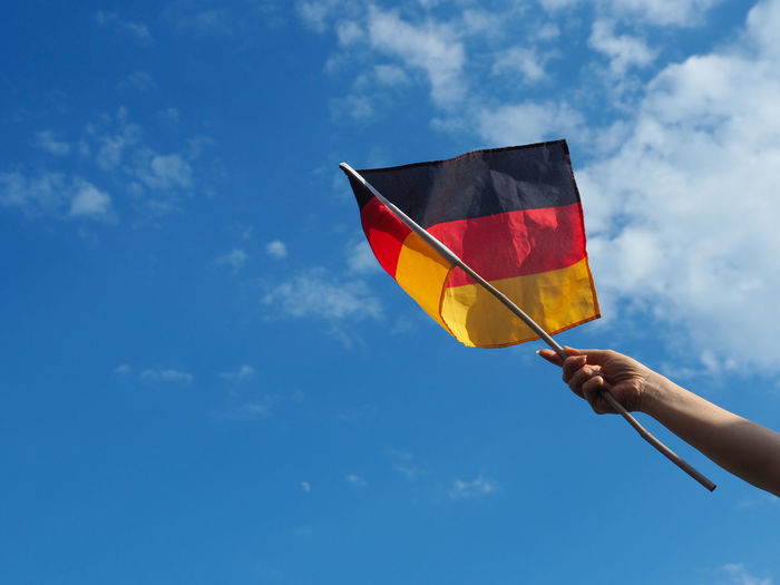 Low angle view of woman holding german flag against sky
