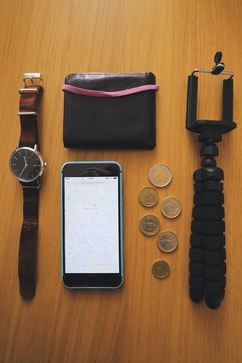 Directly Above Shot Of Mobile Phone And Coins With Personal Accessories On Table