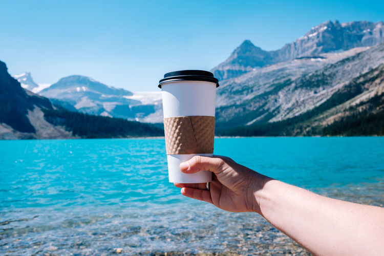 Cropped image of hand holding drink against lake and mountains