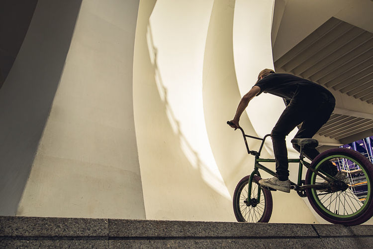 Shadow of man on bicycle by building
