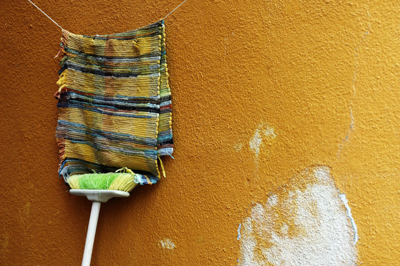Doormat Hanging On Clothesline Against Yellow Wall