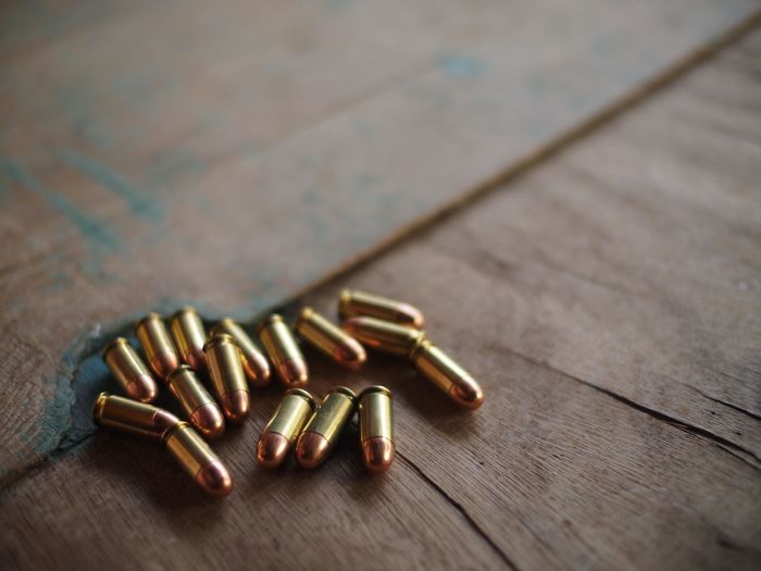 High Angle View Of Bullets On Wooden Table