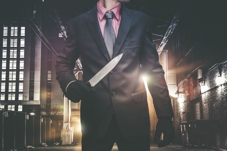Midsection Of Businessman Holding Knife While Standing In Factory