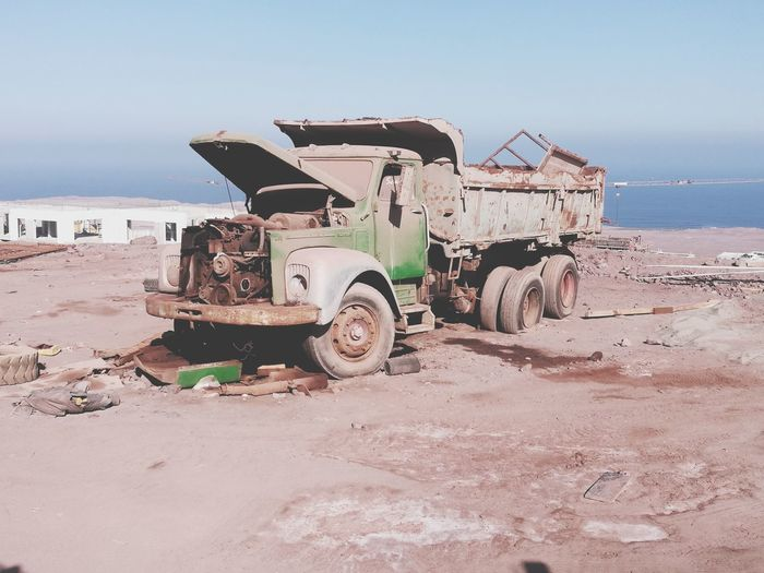 Abandoned truck t beach against sky during sunny day