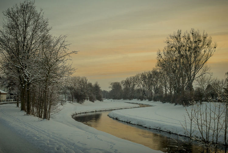 Bare Trees By Frozen Canal Against Sky During Sunset