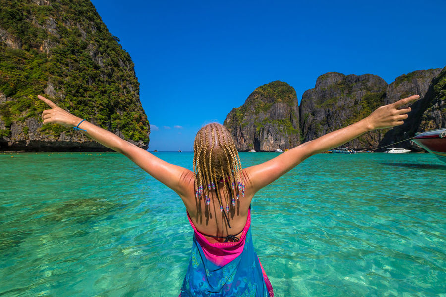 Back of happy and fashionable tourist woman with colorful sarong in turquoise water of Maya Bay famous lagoon of The Beach movie, Phi Phi Leh, Andaman Sea in Thailand Fashionable and happy tourist with sarong and pink wide-brimmed hat making a selfie on tropical famous beach of Nai Harn Beach, Rawai, Phuket, Thailand. Happy tourist enjoys panorama from Sail Rock View Point of kor 8 of Similan Islands National Park, Phang Nga, Thailand, one of the tourist attraction of the Andaman Sea. Happy woman with bikini and shorts, jumping in the air on Ya Nui Beach, a little cove divided by a rocky cape, Phuket, Thailand, Asia. Happy Koh Rok Islands Nui Beach Phang Nga Bay Phuket Thailand Tanning ☀ Thailand Vacations Woman Beach Girl Koh Rok Phang Nga Rawai Sea Seascape Surin Islands Travel Destinations