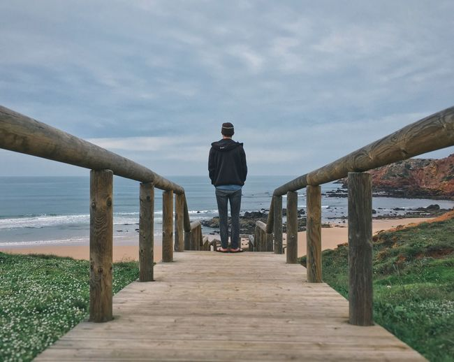 Rear view of man standing on pier at beach against cloudy sky