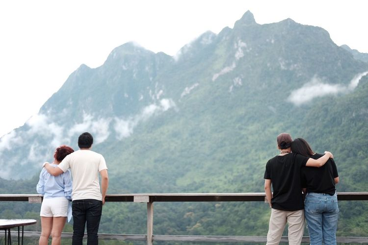 Rear view of couples standing in balcony against mountains