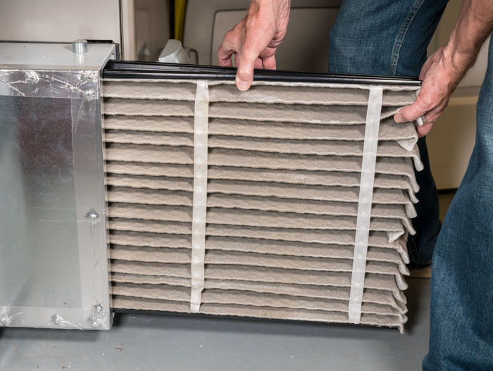 Man changing a large air filter from home HVAC system on furnace or airconditioning system in basement HVAC Air Filter Filter Furnace Heating Heating System Filtration Replacement Replace Basement Human Hand One Person Indoors  Occupation Maintenance Engineer Heater Air Conditioner Clean Dirty Home Maintenance Air Cleaner Man