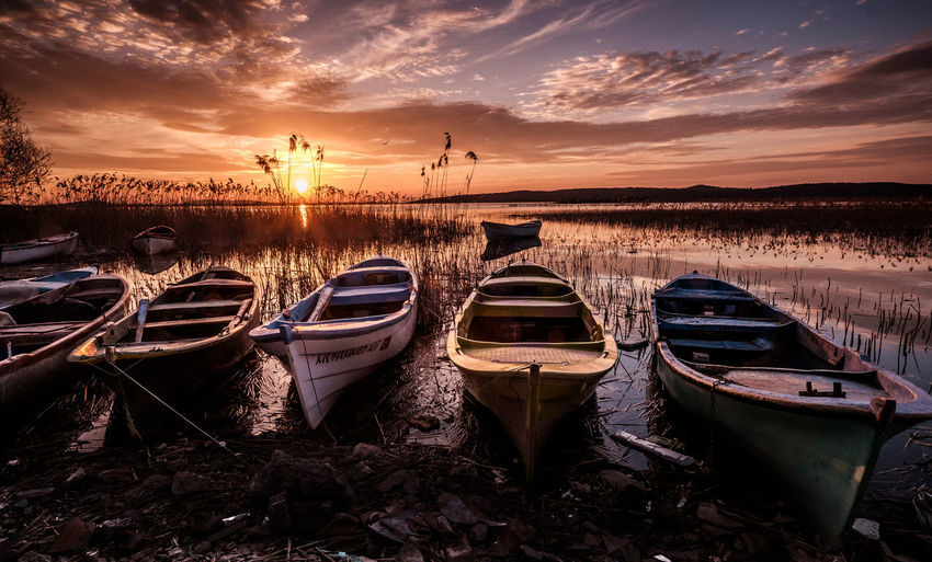 Boats on the lake under sunset. Sky Sunset Cloud - Sky Nautical Vessel Mode Of Transportation Water Transportation Moored Nature Orange Color Tranquility Scenics - Nature Tranquil Scene Beauty In Nature No People Land Outdoors Lake Non-urban Scene Rowboat