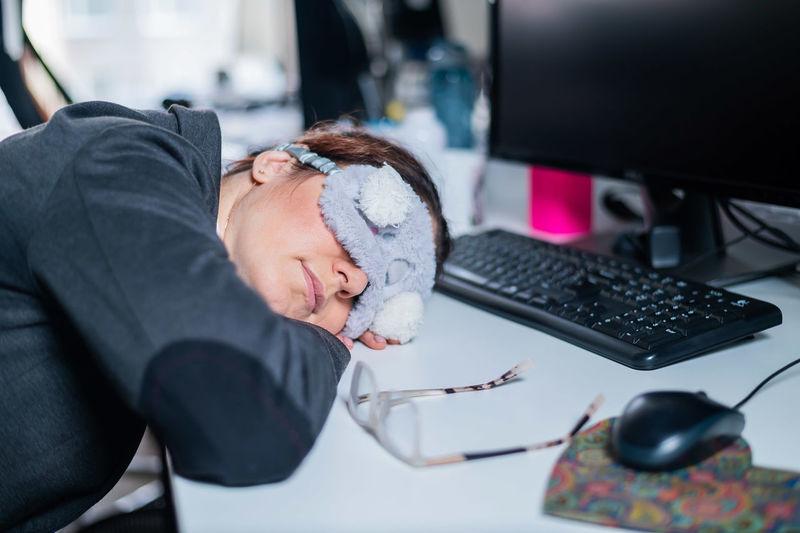 Woman resting on desk in office