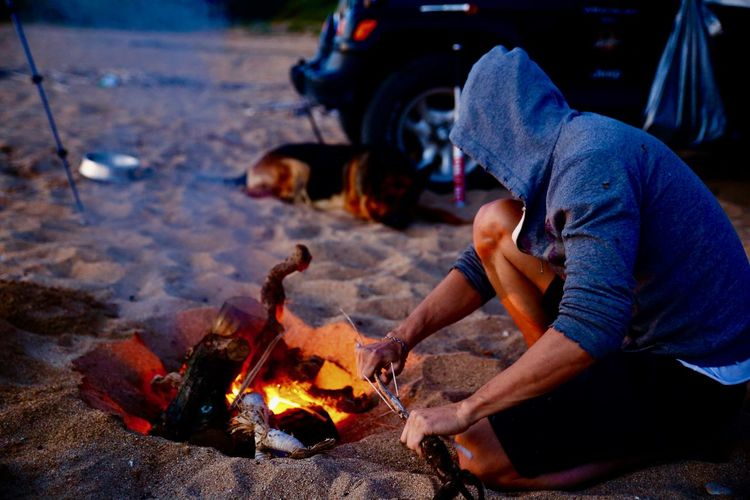 Man breaking sticks by bonfire at beach