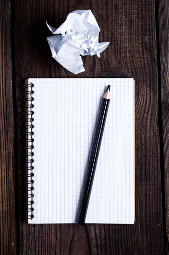 Paper Pen Indoors  Table Crumpled Paper Wood - Material Crumpled Directly Above No People Note Pad Writing Instrument Still Life Crumpled Paper Ball Copy Space High Angle View Spiral Notebook Studio Shot Close-up Creativity Business Blank Fountain Pen Wood Grain