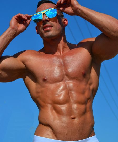 Low Angle View Of Shirtless Young Man Wearing Sunglasses While Standing Against Clear Blue Sky