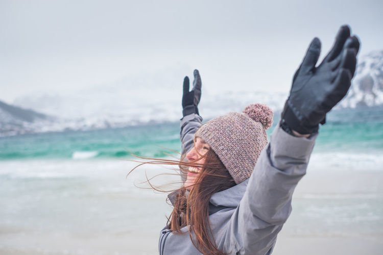 Smiling woman with arms raised standing outdoors during winter