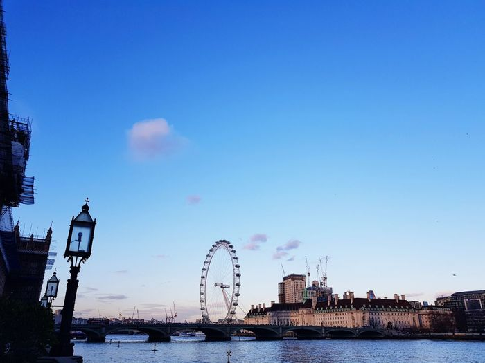 View of ferris wheel in city against blue sky