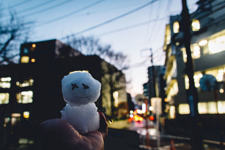 Cropped Hand Holding Snowman Against Illuminated Buildings At Dusk