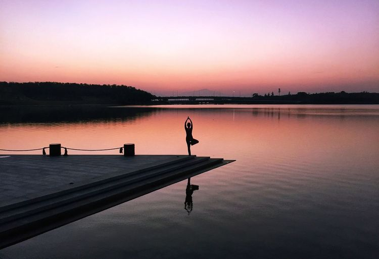 Silhouette Woman Doing Yoga On Pier Over Lake During Sunset