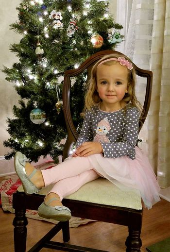Christmas Christmas Trees Innocence Childhood Cute Day Elementary Age Full Length Girls Happiness Indoors  Looking At Camera One Person People Portrait Pretty ın Pink Real People Sitting Smiling Tree