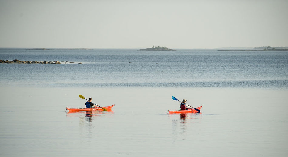 Men Kayaking In Sea Against Clear Sky