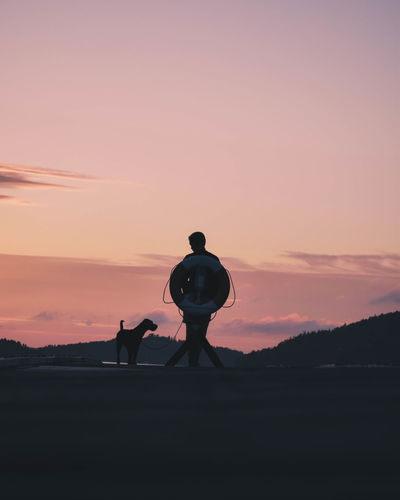 Silhouette man with dog standing on field against sky during sunset