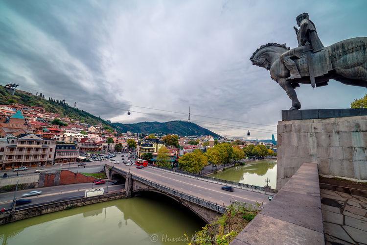 Statue by bridge against sky