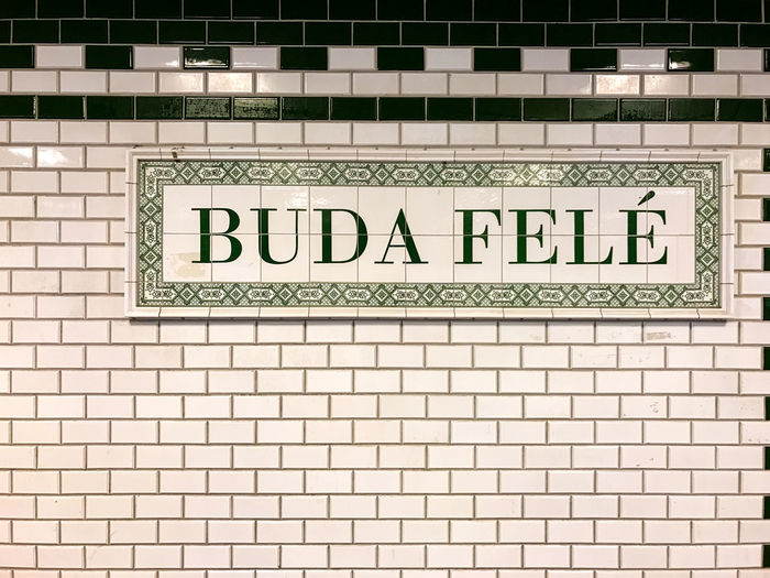 Sign at the metro in Budapest Architecture Brick Brick Wall Built Structure Capital Letter Close-up Communication Flooring Guidance Indoors  Information Message No People Non-western Script Script Sign Text Tile Wall Wall - Building Feature Western Script