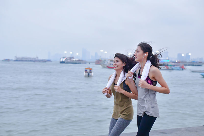 Sports concept. Beautiful girl is exercising on the beach with running. Beautiful girl is happy to exercise. Beautiful girls like to exercise by running. People are exercising on the beach. Terrestrial Sports Active Activities Activity Asian  Athlete Blue Boardwalk Chinese Clothes Endurance Exercise Exert Female Fitness Freedom Game Girl Happiness Happy HEAL Health Healthcare Healthful Healthy Japanese  Jogger Korean Legs Lifestyle Morning Motion Ocean person Relax Relaxation Runner Running Sea Seaside Sky Sports Stamina Trail Training Vitality Walking Warm Up Woman Young