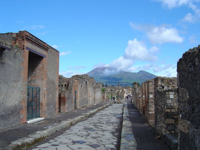 Narrow Walkway Along Buildings And Mountains Against Blue Sky