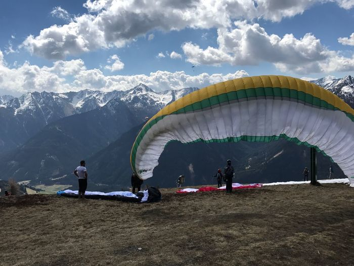 People with parachutes on mountain against sky