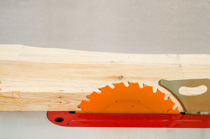Cutting the board on a circular saw in a woodworking workshop Art And Craft Close-up DIY Equipment Flooring Hand Saw Hand Tool High Angle View Home Improvement Indoors  Metal No People Orange Color Red Still Life Table Tool White Color Wood Wood - Material Work Tool Yellow