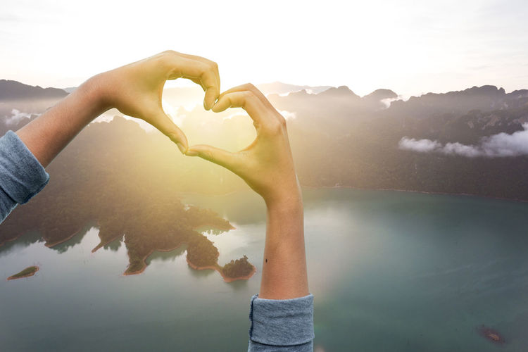 Hand shaping a love hand .and Sunrise background. love concept Water Human Hand Hand Nature Real People Human Body Part Sky Lake Lifestyles Beauty In Nature Mountain Leisure Activity Day Sunlight Non-urban Scene Love Outdoors Positive Emotion