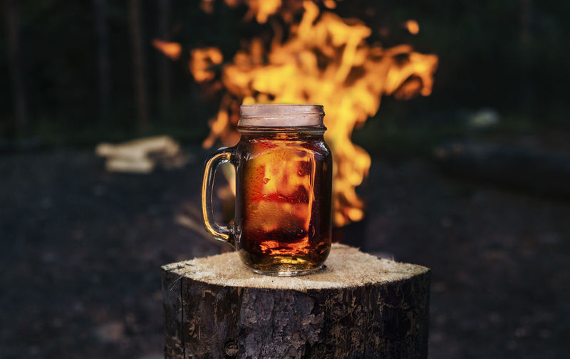 Close-up of drink in jar against fire