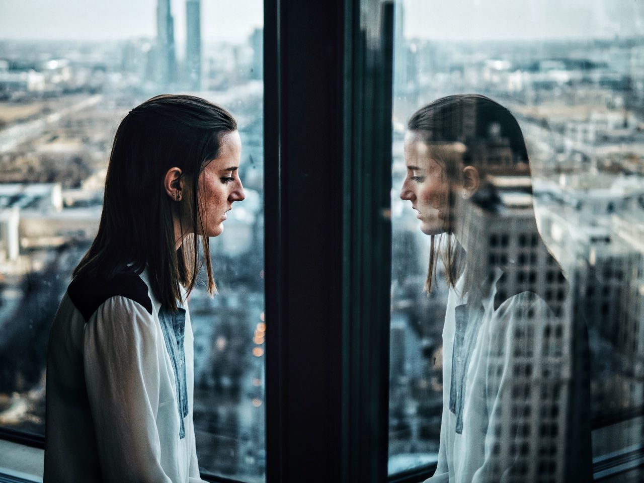 Side view of woman looking through window with reflection