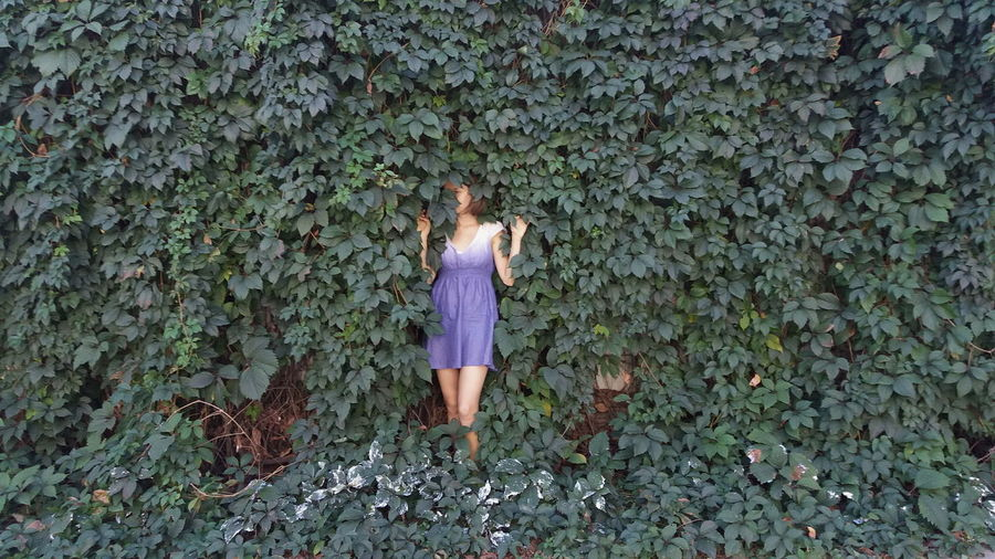 Woman standing by creeper plant