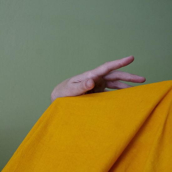 Close-up of woman hand against yellow wall