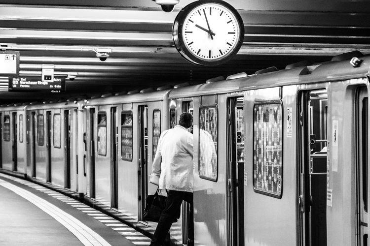 Rear View Of Man Entering Train At Railroad Station